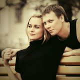 Happy young couple in love sitting on bench outdoor. Happy young man and woman in love sitting on bench outdoor Royalty Free Stock Image