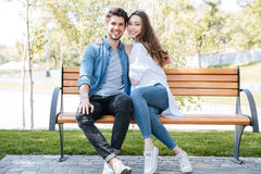 Happy young couple in love sitting on a park bench Stock Image