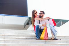 Happy Young Couple in Love sitting at the stairs with shopping bags royalty free stock photography