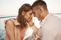 Happy young couple in love smiling and enjoying boat trip on the sea. Romance and vacation concept. Boyfriend tenderly. Touches her cheek and girlfriend feels Royalty Free Stock Images