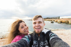 Happy young couple in love takes selfie portrait on the beach in Cyprus in autumn or winter. Pretty tourists make funny. Happy young couple in love takes selfie stock photos