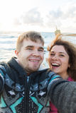 Happy young couple in love takes selfie portrait on the beach in Cyprus in autumn or winter. Pretty tourists make funny stock photos