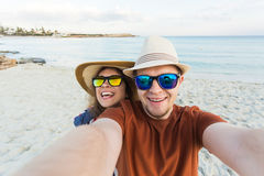 Happy young couple in love takes selfie portrait on the beach in Cyprus. Pretty tourists make funny photos for travel Royalty Free Stock Photography
