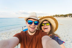 Happy young couple in love takes selfie portrait on the beach in Cyprus. Pretty tourists make funny photos for travel Royalty Free Stock Photos