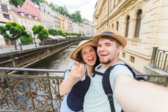 Happy young couple in love takes selfie portrait in Karlovy Vary in Czech Republic. Pretty tourists make funny photos. For travel blog in Europe royalty free stock photos