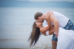 Happy young couple in love walking on the beach Stock Photos