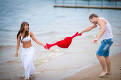 Happy young couple in love walking on the beach Stock Image