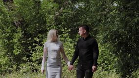 Happy young couple in love walking in the sunny forest holding hands.  stock video