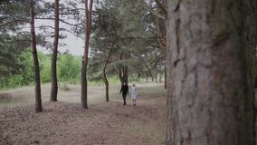 Happy young couple in love walking in the sunny forest holding hands.  stock video footage