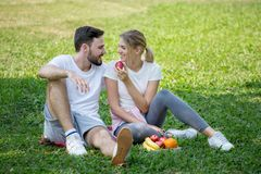 Happy young couple loving fitness in sportswear relaxing at park eating apple together in morning time. sport people sitting. Taking a break after exercises stock images