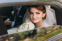 Happy young couple in luxurious car after their wedding. Focus on beautiful bride, smiling at camera Stock Image