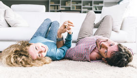Happy young couple lyind on the carpet Royalty Free Stock Images