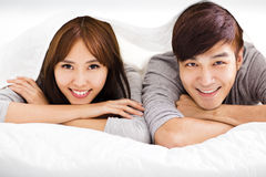 Happy young couple lying in a bed Royalty Free Stock Photography