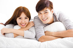 Happy young couple lying in a bed Stock Image