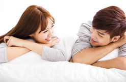 Happy young couple lying in a bed Royalty Free Stock Image