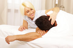 Happy young couple lying on the bed Royalty Free Stock Photos