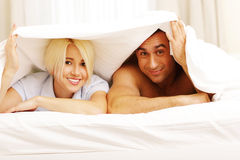 Happy young couple lying on the bed Stock Photography