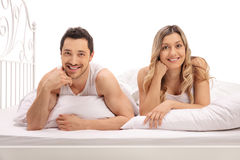 Happy young couple lying in bed Royalty Free Stock Photos