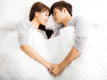 Happy young couple lying in a bed Stock Photo