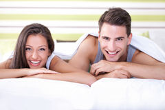 Happy young couple lying on bed Royalty Free Stock Images