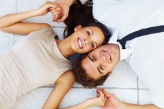 Happy young couple lying down on floor Stock Image