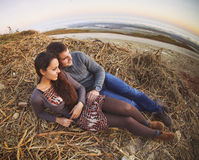 Happy young couple lying down smiling at autumn background Stock Photo