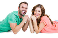 Happy young couple lying on floor looking at camera Royalty Free Stock Photos