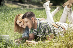 Happy young couple lying on the grass, looking at laptop and smi. Ling. Relationship  and learning concept Stock Photo
