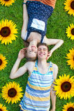 Happy, young couple lying in the grass. Happy teenager couple lying on a sunny meadow with sunflowers Royalty Free Stock Photo
