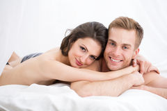Happy Young Couple Lying In White Bed Stock Photos