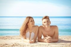 Happy young couple lying on sea beach. At resort Stock Photo
