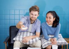 Happy young couple lying on the sofa with push remote at home watching TV. Royalty Free Stock Photos