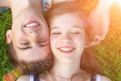 Happy, young couple lying in the sun. Happy teenager couple lying on a sunny meadow royalty free stock image