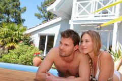 Happy young couple lying by the swimming pool Stock Photography