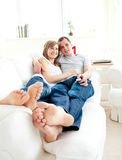 Happy young couple lying together on the couch Royalty Free Stock Image