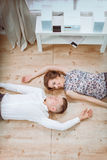 Happy young couple lying together on the floor Stock Images