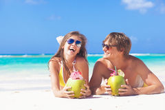 Happy young couple lying on a tropical beach in Barbados and drinking a coconut cocktail. Remote tropical beaches and countries. travel concept Royalty Free Stock Photo