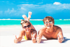 Happy young couple lying at a tropical beach. thumbs up. gesture Stock Image