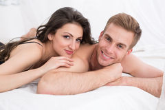 Happy young couple lying in white bed. Looking at the camera. Girl hugging guy. Morning light Stock Image