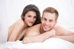 Happy young couple lying in white bed Stock Image