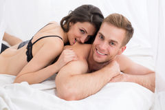 Happy young couple lying in white bed. Looking at the camera. Girl hugging guy and playfully biting a guy in the back. Morning light Royalty Free Stock Photos