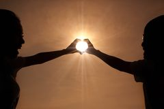 Happy young couple making heart shape. With hands  at sunset Royalty Free Stock Image