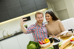 Happy young couple making selfie while cooking Royalty Free Stock Photo