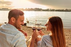 Happy young couple making a toast with red wine. Enjoying picnic at the beach. White swans swimming and sunset over water in the background. Romance, dating stock photography
