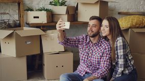 Happy young couple is making video call with smartphone after relocation. They are greeting friends, showing new house