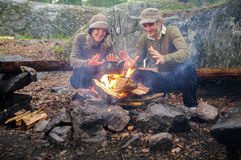 Happy young couple man, woman sitting in front of campfire at day and warm hands Royalty Free Stock Photos