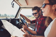 Happy young couple with a map in the car royalty free stock photo
