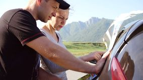 Happy young couple with a map in the car. They are using map on road trip.  stock footage