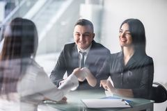 Happy young couple meeting with a broker in her office leaning over the desk to shake hands, view from behind the female agent tho royalty free stock photos