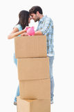 Happy young couple with moving boxes and piggy bank Stock Images